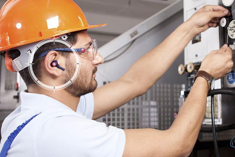 Technician working in a noisy environment with hearing protection